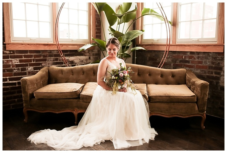 bride sitting looking down with bouquet in lap