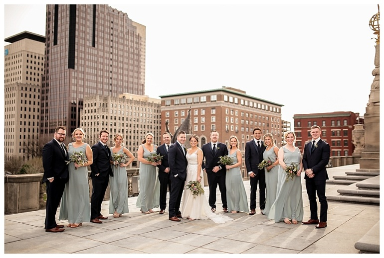 wedding party posed with city skyline in backdrop